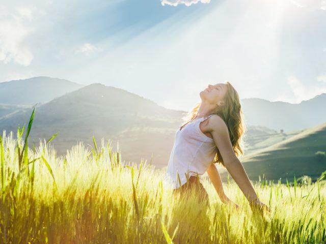 Frau steht im Feld im Sonnenlicht
