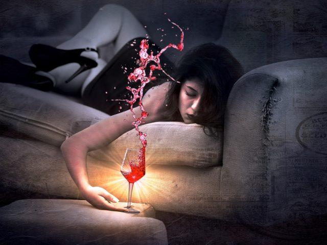 Frau auf Sofa mit Weinglas